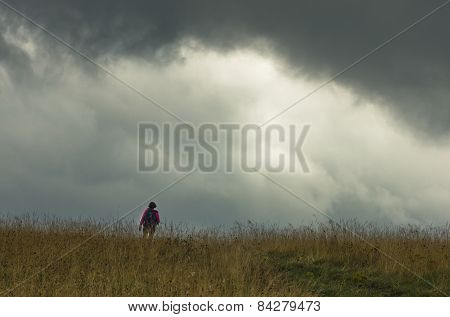 Trekking through prairie hillside under dark clouds