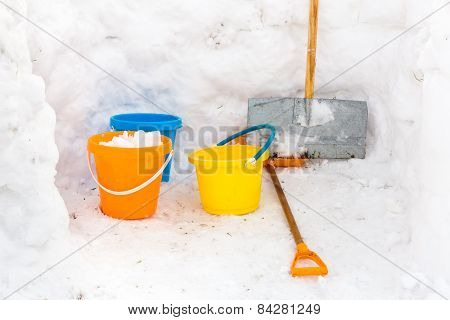 Hut with walls of snow and colorful buckets