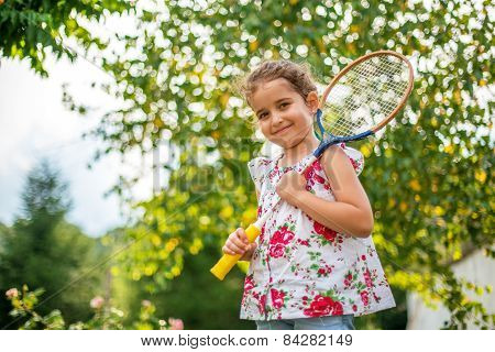 Portrait Of A Smiling Little Girl Holding Tennis Racket