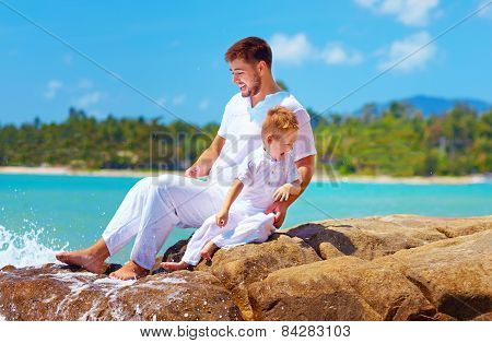 Water Splashing On Happy Father And Son On Tropical Beach