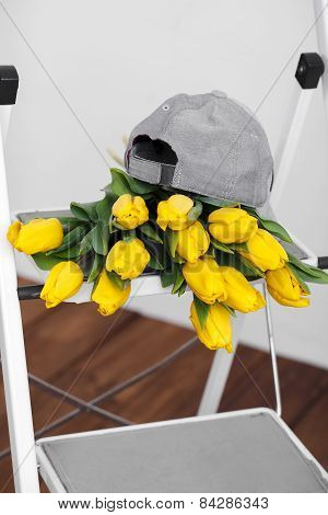 A large bouquet of yellow tulips lies on the white ladder.