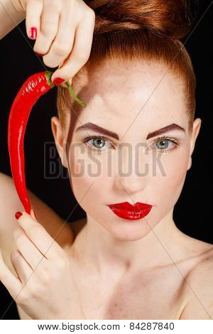 Sexy brunette girl with red cayennes isolated on black