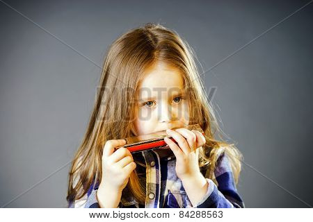 Cute Little Girl Playing Harmonica
