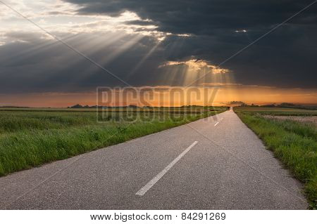 Driving On An Empty Country Road At Sunset