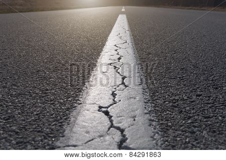 Straight Line On Asphalt Full Of Cracks