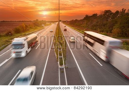Truck And Bus On The Motorway At Sunset
