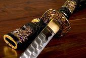 foto of longsword  - Ornate Japanese Samurai sword on wooden table - JPG