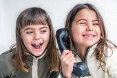picture of 7-year-old  - Seven year old girl talking on the old vintage phone and her sister eavesdropping her conversation. White background.