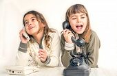stock photo of 7-year-old  - Two seven year old girls talking on the old vintage phones with the white background