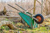 picture of upside  - Upside down wheelbarrow leaning against net fence in early spring - JPG