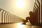 foto of adolescent  - Sad teenager girl depressed sitting in the floor of a bridge on the beach at sunset - JPG