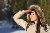 pic of forehead  - Woman looking forward with the hand on forehead in a forest in winter holidays - JPG