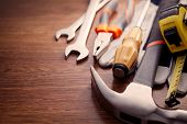 stock photo of hand tools  - Close up Hand Work Tools on Top of a Wooden Table Emphasizing Pliers Hammer Screw Drivers and Gloves - JPG