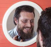 stock photo of beard  - Bearded man cutting his beard with scissors - JPG