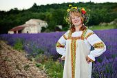 image of farmhouse  - Peasant girl in a flowers wreath dressed in a russians gown stands on the dirt road along lavender field farmhouse on background - JPG