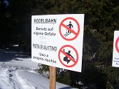 stock photo of toboggan  - A signage before a toboggan run with regard to prohibition for skiers - JPG