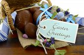 picture of easter basket eggs  - Happy Easter basket hamper of chocolate Easter Eggs and flower on dark wood table - JPG