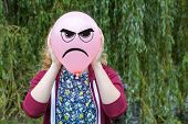 pic of bitchy  - Girl holding balloon with angry facial expression with willow tree background - JPG