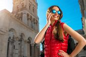 pic of knapsack  - Young woman dressed in sportswear with smart phone traveling in the old city center - JPG