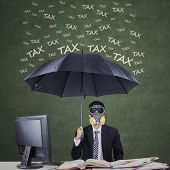 image of gas mask  - Businessman wearing a gas mask and umbrella to protect him from tax - JPG