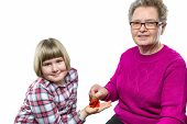 picture of granddaughters  - Grandmother putting euro coin in granddaughter - JPG