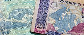 stock photo of karakoram  - Used banknotes from India and Pakistan showing parts of the Himalaya mountain range - JPG