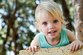 stock photo of human-rights  - Adorable smiling toddler girl looking right in camera shallow focus - JPG