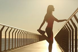 stock photo of bridge  - Runner silhouette doing stretching exercises at sunset in a bridge on the beach - JPG