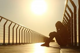 pic of bridge  - Sad teenager girl depressed sitting in the floor of a bridge on the beach at sunset - JPG