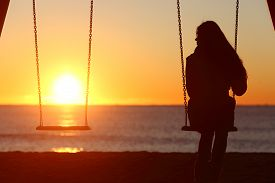 stock photo of swing  - Single woman alone swinging on the beach and looking the other seat missing a boyfriend - JPG