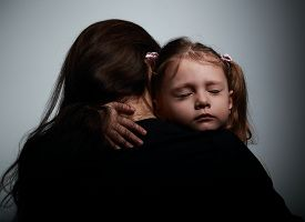 stock photo of sad  - Sad crying daughter hugging her mother with sad face on dark shadows background - JPG