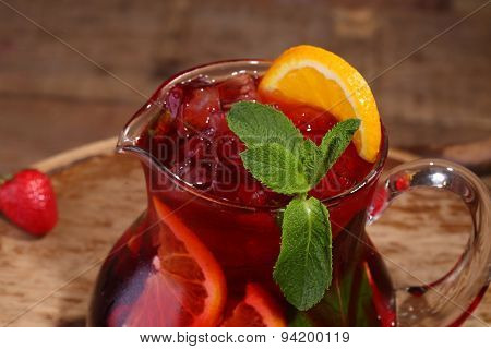Wine Of Sangrija In A Transparent Jug On A Wooden Table With An Orange And A Strawberry