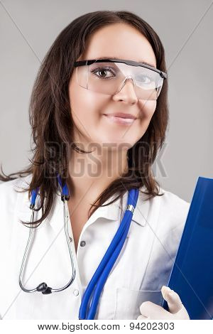 Medical Concept: Caucasian Medical Female Doctor With Stethoscope And Folder. Over Gray Background.