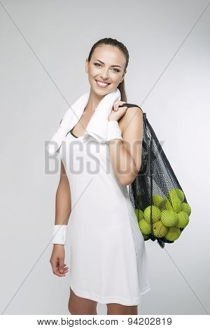 Tennis Concept And Ideas: Portrait Of Professional Female Tennis Player Holding Plenty Of Balls In M