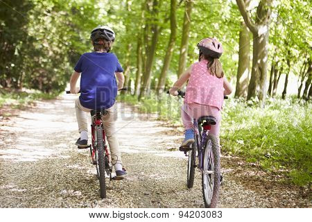 Rear View Of Two Children On Cycle Ride In Countryside