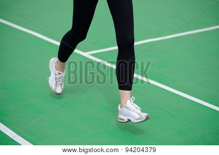 Woman Athlete Runner Feet Running on the Green Running Track. Fitness and Workout Wellness Concept.