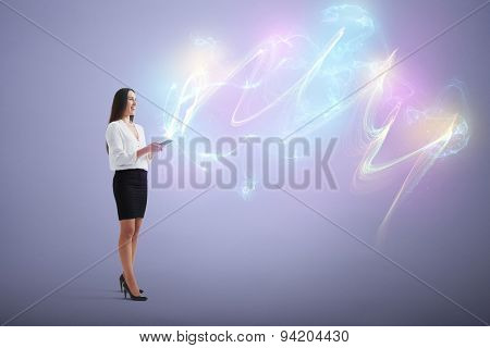 full length portrait of smiley woman touching smartphone and shiny magic comes from screen