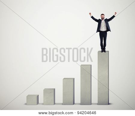 happy businessman winner standing on top of concrete diagram over light grey diagram