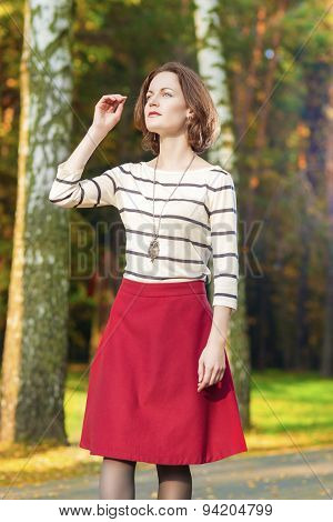 Dreaming Caucasian Brunette Woman In Fashion Clothing Posing In Fall Forest Outdoors.
