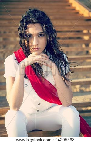 Girl With A Red Scarf Sitting On The Stairs