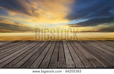 wood terrace and golden light on sea water