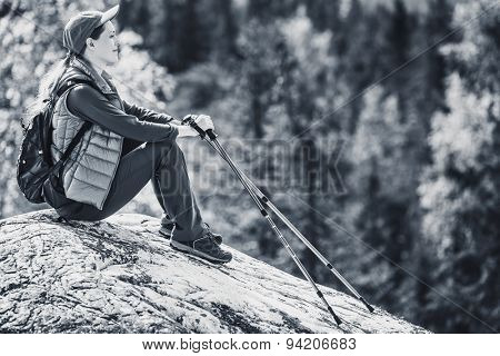 Young woman tourist sitting on mountain top and looking aside on forest. Black and white colors.