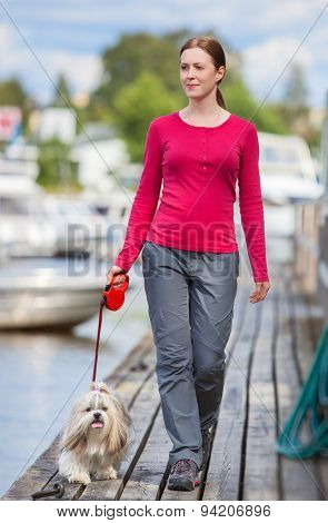 Young woman with shih-tzu dog walking on town quay with boats.