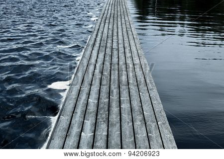 Long floating wooden bridge on water surface.