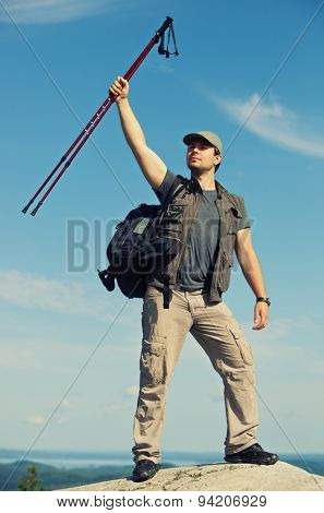 Young man tourist with backpack standing on mountain top and holding sticks above head.