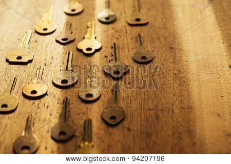 Various vintage brass keys aligned in the same direction on a old wooden desk. Security and encryption, concept image. Shallow depth of field.