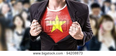 Businessman stretching suit with Vietnam with a crowd people on background