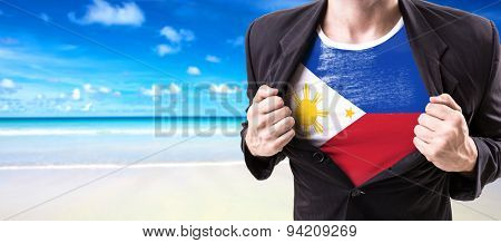 Businessman stretching suit with Philippines Flag on beach background