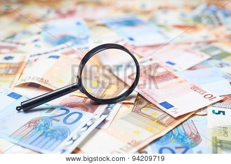 Magnifying glass over the pile of money
