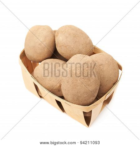 Pile of earth dirty potatoes in a basket